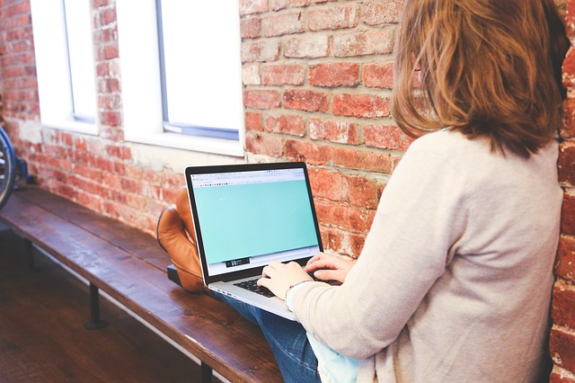 žena s počítačem na parapetu