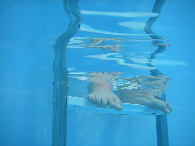 nohy člověka v čisté bazénové vodě