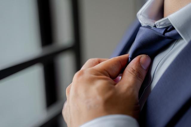 muž uvazující si kravatu u obleku