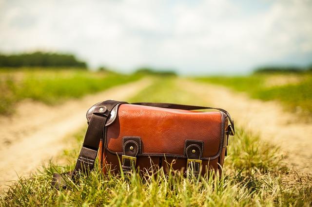 hnědá kožená kabelka na polní cestě